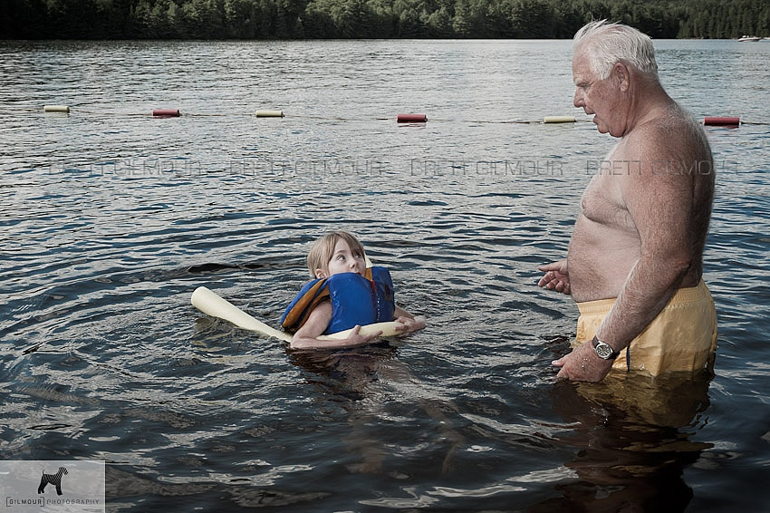 Photo of grandfather teaching granddaughter to swim