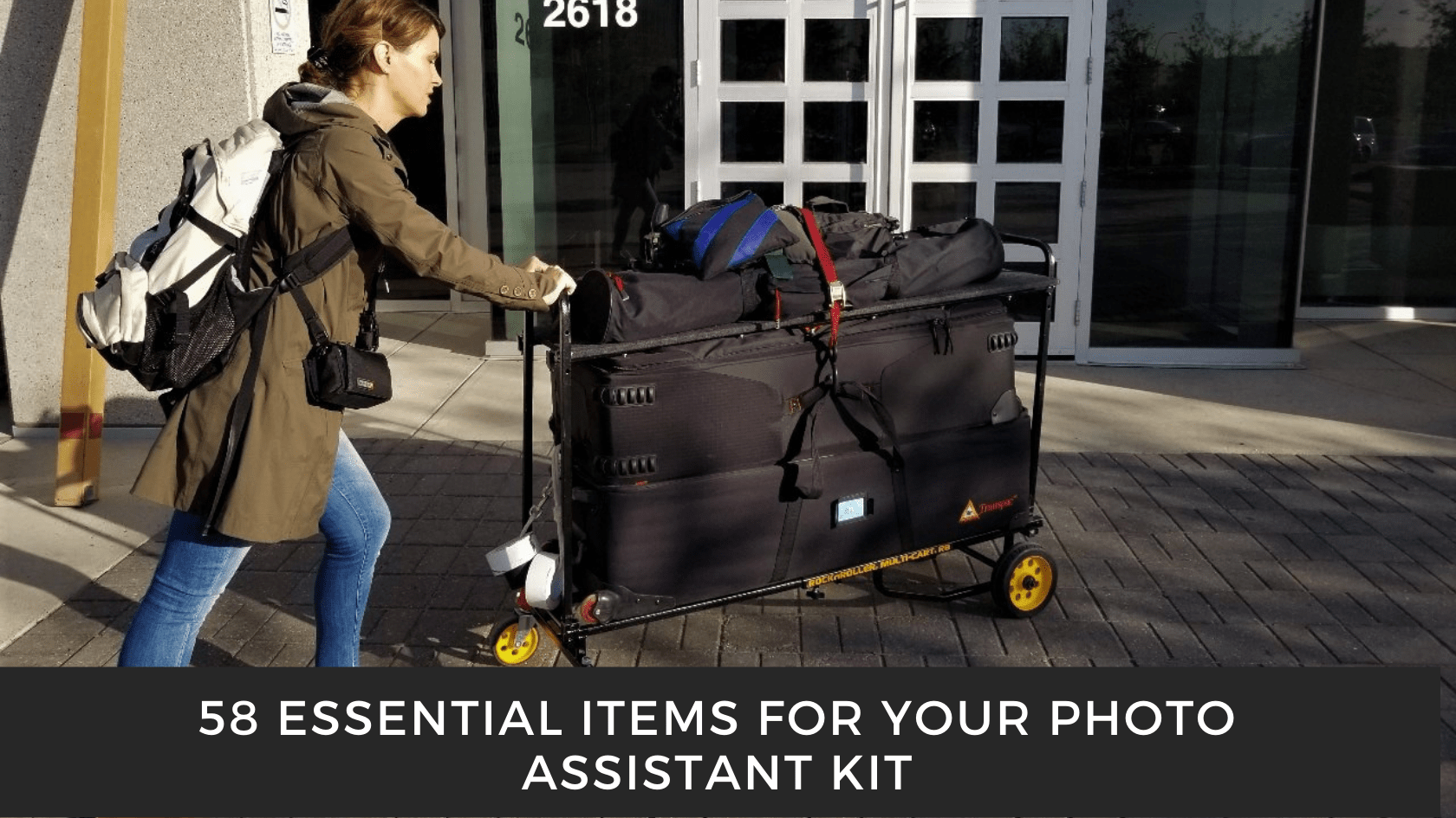 Photo of a woman pushing a photo assistant kit on a studio cart