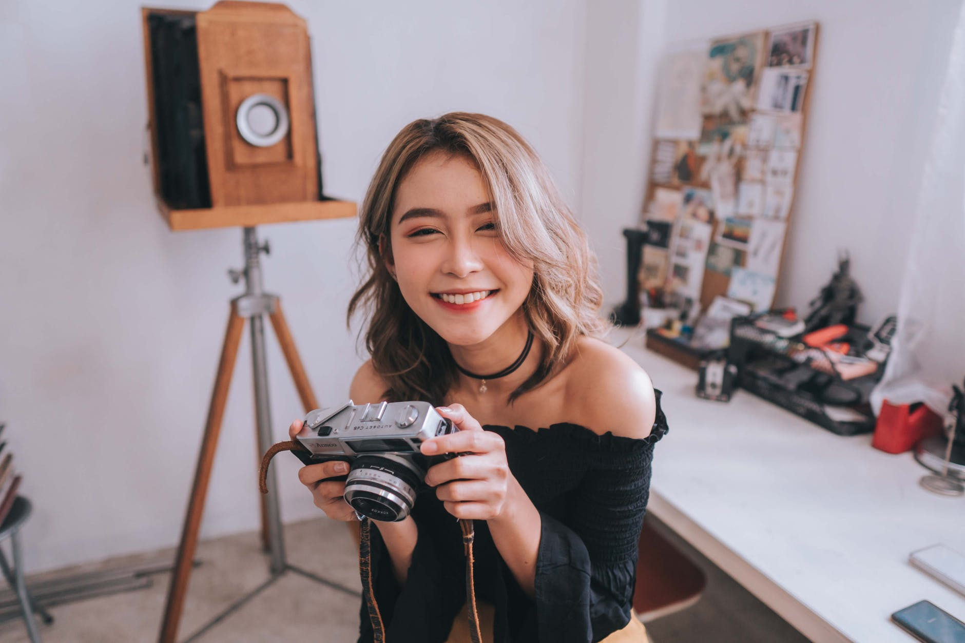 Asian professional photographer woman holding and SLR camera in a photo studio.