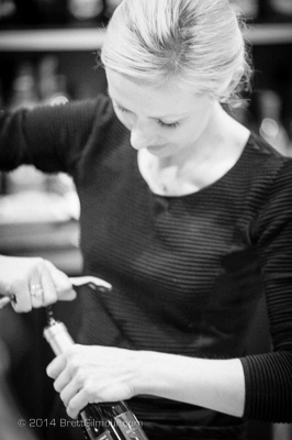 Photo of woman opening wine