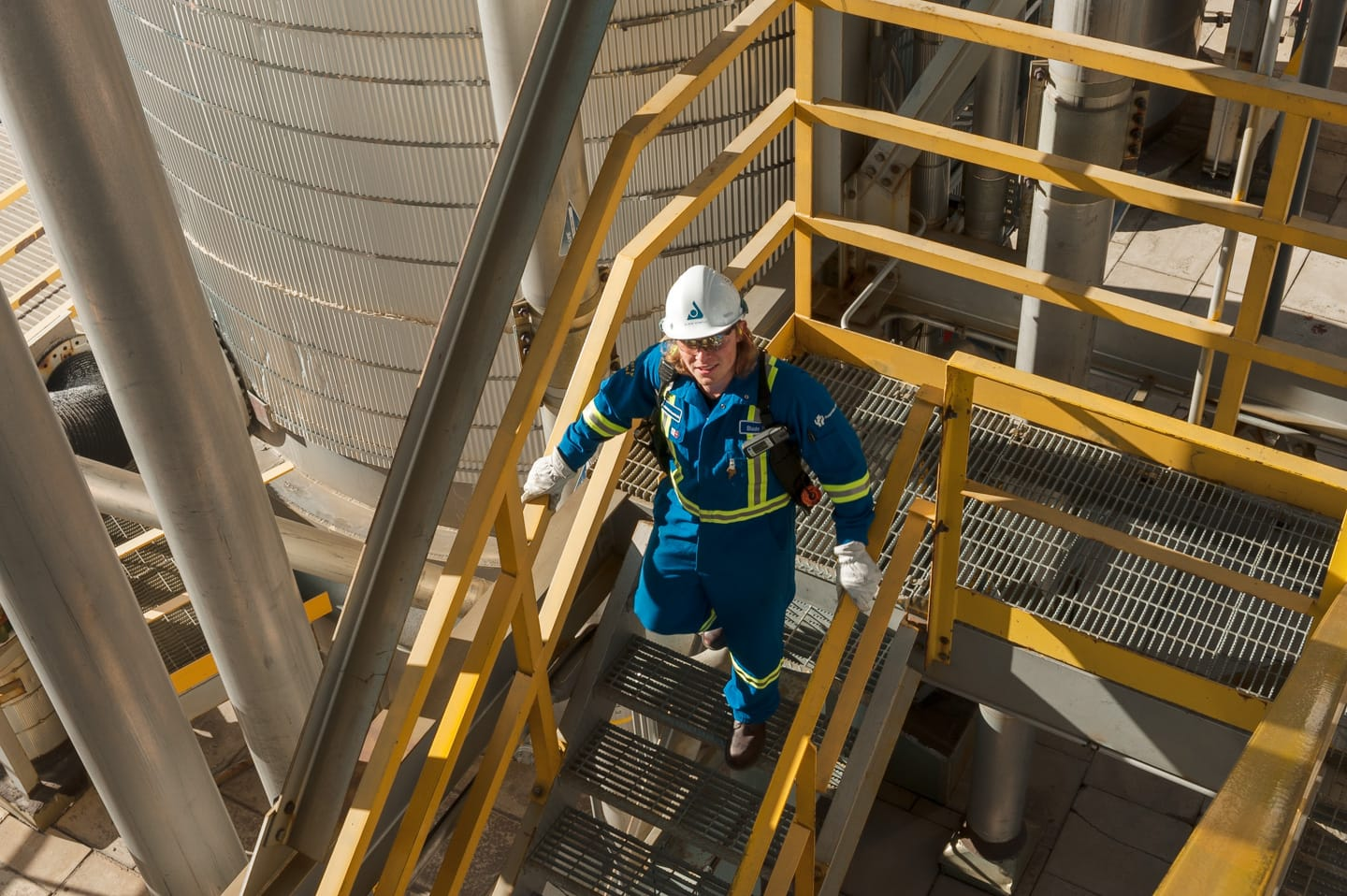 Commercial photography of a man walking down at staircase at an industrial plant