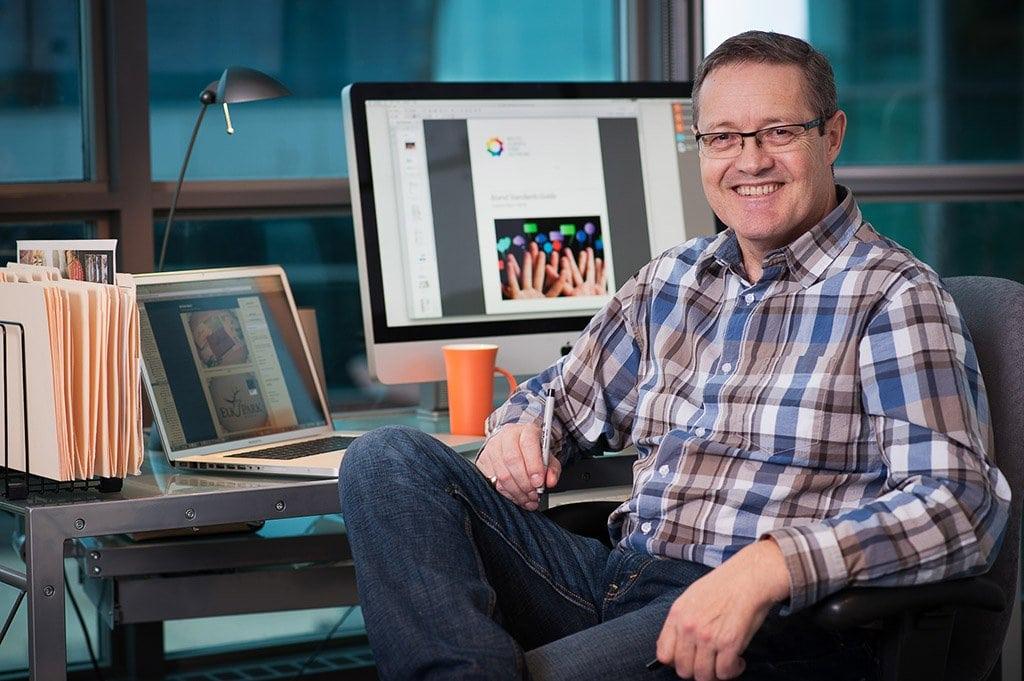 Environmental portrait of a graphic designer in his graphic design studio in Calgary, Alberta